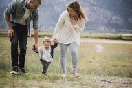 Parents walking with baby son in rural field - CAIF22034
