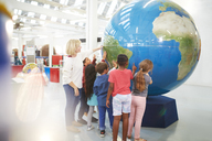 Teacher and students touching large globe in science center - CAIF22037