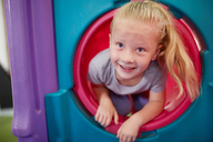 Portrait cute, happy girl playing in tube slide - CAIF22079