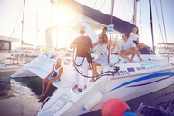 Friends relaxing on catamaran ins sunny harbor - CAIF22118