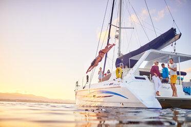 Young woman diving off catamaran into ocean - CAIF22121