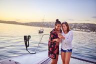 Young women using smart phone on catamaran - CAIF22136