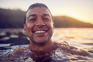 Close up portrait smiling, carefree man swimming in ocean - CAIF22139
