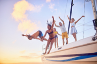 Playful friends jumping off boat - CAIF22148