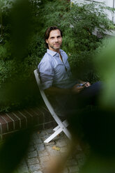 Portrait of smiling man sitting on chair in garden using cell phone - HHLMF00369