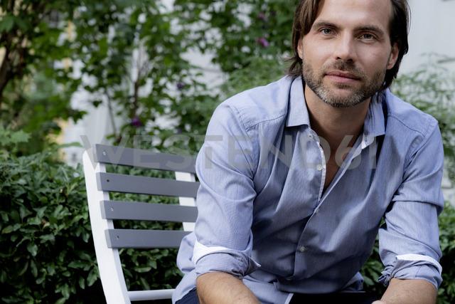 Portrait of confident man sitting on chair in garden - HHLMF00372 - harrylidy/Westend61
