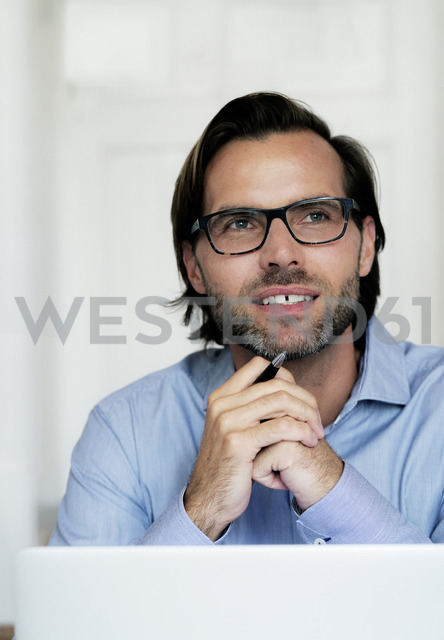 Smiling businessman wearing glasses and holding pen - HHLMF00375 - harrylidy/Westend61