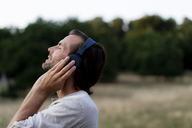 Smiling man listening to music with headphones in the nature - HHLMF00384