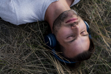 Relaxed man lying in field listening to music with headphones - HHLMF00387