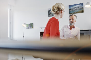 Two colleagues talking at desk in office - RHF02092