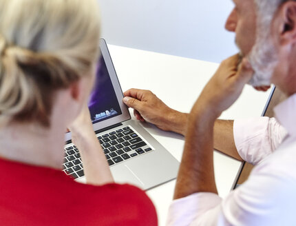 Two colleagues working on laptop at desk in office - RHF02104
