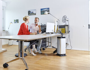 Two colleagues talking at desk in office - RHF02122