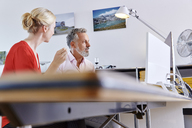 Two colleagues working together at desk in office - RHF02125