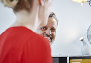 Smiling mature man looking at female colleague in office - RHF02128