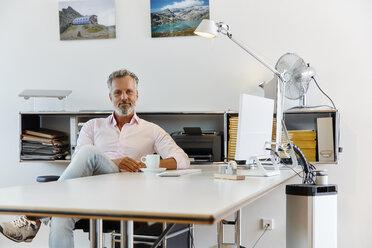 Portrait of confident businessman sitting at desk in office - RHF02131