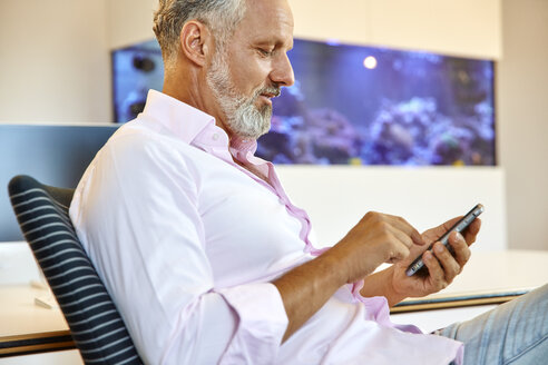 Businessman sitting in office using cell phone - RHF02137