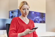 Young woman sitting at desk in office using cell phone - RHF02140