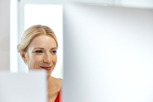 Portrait of smiling young woman working on computer - RHF02143