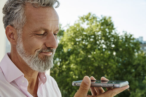 Portrait of smiling mature man holding smartphone outdoors - RHF02152