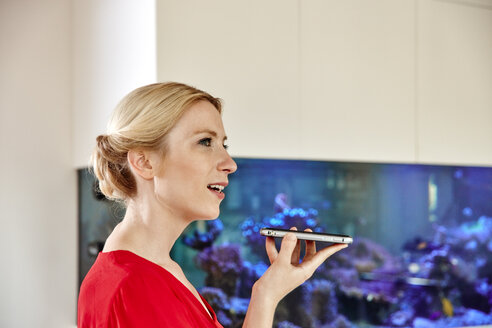 Young woman using smartphone in office with an aquarium - RHF02158