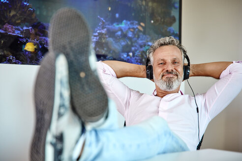 Relaxed mature man listening to music with headphones in front of aquarium - RHF02161