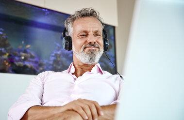 Businessman with headphones using laptop at desk in front of aquarium - RHF02164