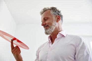 Smiling mature man holding red vinyl record - RHF02167