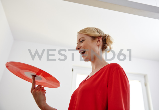 Happy young woman holding red vinyl record - RHF02170