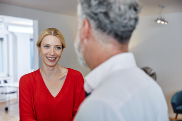 Smiling young woman looking at mature colleague in office - RHF02176
