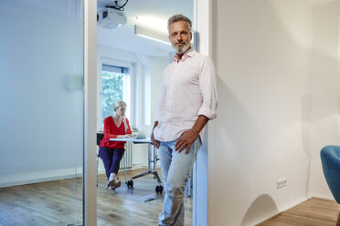 Portrait of mature man leaning against doorframe in office with colleague in background - RHF02188