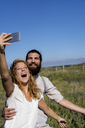 Young couple taking smartphone selfies on the beach - HHLMF00397