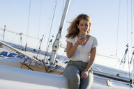 Beautiful woman sitting on a boat, using smartphone - HHLMF00448