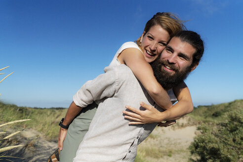 Young man carrying his girlfriend piggyback in the dunes - HHLMF00469