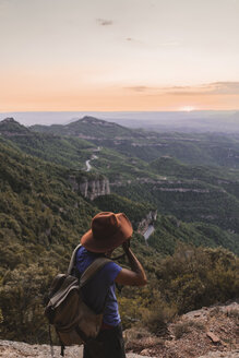 Spain, Barcelona, Montserrat, man with backpack taking photo of view at sunset - AFVF01550