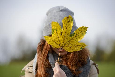 Teenage girl hiding behind autumn leaf - LBF02043