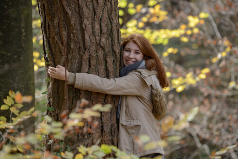 Portrait of happy teenage girl hugging tree trunk in autumnal forest - LBF02049