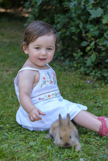Portrait of content baby girl sittting on a meadow with young bunny - LBF02055
