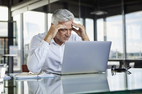 Stressed businessman sitting at desk with laptop, holding his head - RBF06580
