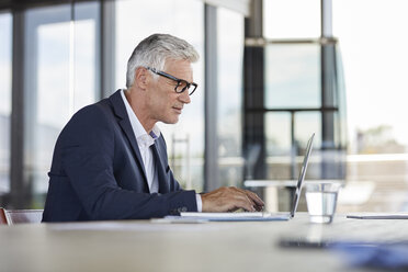 Businessman working in office, using laptop - RBF06607