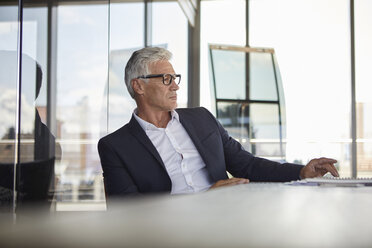 Businessman sitting in office, thinking - RBF06613