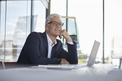 Businessman sitting in office, thinking - RBF06616