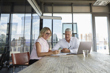 Businessman snd woman sitting in office, discussing project - RBF06619