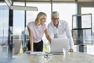 Businessman and woman discussing project in office - RBF06628