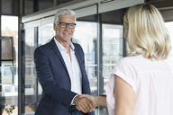 Businessman and woman shaking hands in office - RBF06637