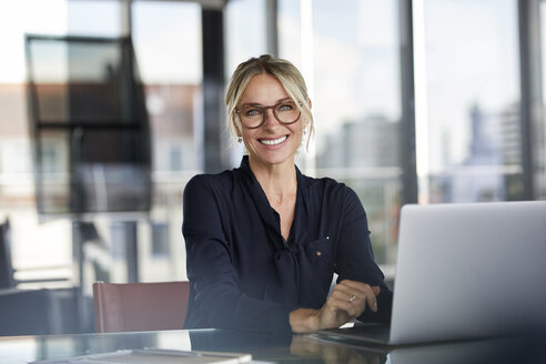 Businesswoman sitting at desk, using laptop, smiling friendly - RBF06640