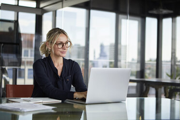 Businesswoman working in office, using laptop - RBF06643