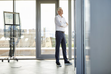 Successful businessman standing in office, looking out of window, with arms crossed - RBF06661