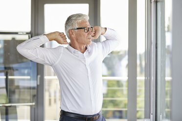 Confident businessman standing in office, stretching at the window - RBF06673