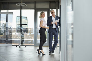 Businessman and woman standing in office, discussing project, holding documents - RBF06679
