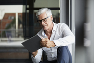 Serene businessman sitting on ground in office, using digital tablet - RBF06688
